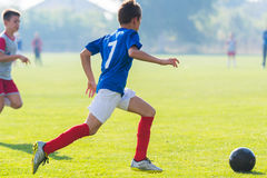 Boy kicking soccer ball Royalty Free Stock Images