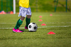 Boy kicking soccer ball on sports field. Soccer football trainin. Soccer football training session for children Stock Photography
