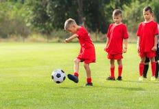 Boy kicking soccer ball at training. On sports field stock image
