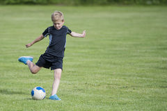 Boy kicking soccer ball Stock Photography