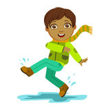 Boy Kicking Water With Foot, Kid In Autumn Clothes In Fall Season Enjoyingn Rain And Rainy Weather, Splashes And Puddles Royalty Free Stock Photography