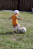 Boy kicks football Stock Images