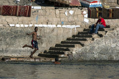 A boy kicks a paper football into the River Nile at Aswan in Egypt. A boy jumps of a set of stairs to kick a paper football into the River Nile at Aswan in Royalty Free Stock Photography