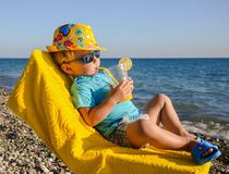 Boy kid in armchair with juice glass on beach Stock Image