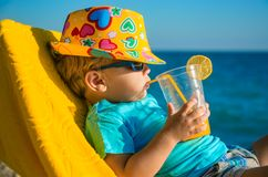 Boy kid in armchair with juice glass on beach. Against sea Stock Photos