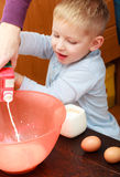 Boy kid baking cake. Child pouring mik into a bowl. Kitchen. Royalty Free Stock Images