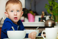 Boy kid child eating corn flakes breakfast meal at the table Stock Photo