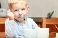 Boy kid child eating corn flakes breakfast meal at the table Royalty Free Stock Photos