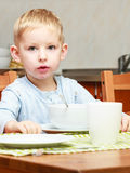 Boy kid child eating corn flakes breakfast meal at the table Royalty Free Stock Image