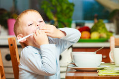 Boy kid child eating corn flakes breakfast morning meal at home. Happy childhood. Blond boy kid child playing with spoon eating corn flakes cereal with milk royalty free stock photos