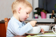 Boy kid child eating corn flakes breakfast morning meal at home. Stock Photos