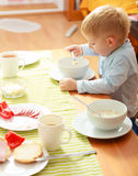 Boy kid child eating corn flakes breakfast morning meal at home. Happy childhood. Blond boy kid child eating corn flakes cereal with milk breakfast morning meal stock photo