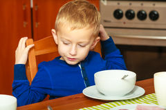 Boy kid child eating corn flakes breakfast morning meal at home. Happy childhood. Blond boy kid child eating corn flakes cereal with milk breakfast morning meal royalty free stock photos