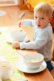 Boy kid child eating corn flakes breakfast morning meal at home. Royalty Free Stock Photo