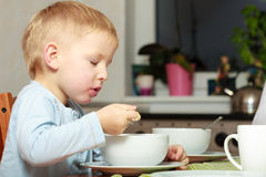 Boy kid child eating corn flakes breakfast morning meal at home. Happy childhood. Blond boy kid child eating corn flakes cereal with milk breakfast morning meal royalty free stock photo