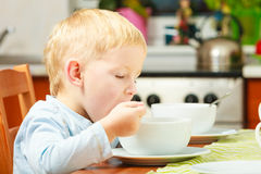 Boy kid child eating corn flakes breakfast morning meal at home. Happy childhood. Blond boy kid child eating corn flakes cereal with milk breakfast morning meal stock photography