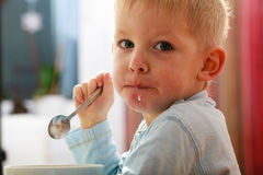 Boy kid child eating corn flakes breakfast morning meal at home. Happy childhood. Blond boy kid child eating corn flakes cereal with milk breakfast morning meal stock images