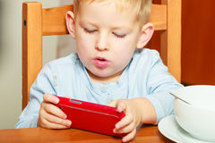 Boy kid child eating corn flakes breakfast playing mobile phone. Happy childhood. Blond boy kid child eating corn flakes cereal with milk breakfast morning meal stock photography
