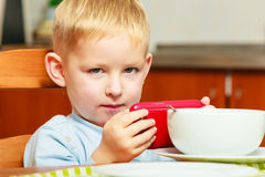 Boy kid child eating corn flakes breakfast playing mobile phone. Happy childhood. Blond boy kid child eating corn flakes cereal with milk breakfast morning meal stock image