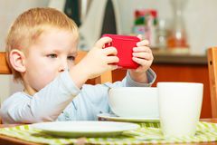 Boy kid child eating corn flakes breakfast playing mobile phone Stock Photography