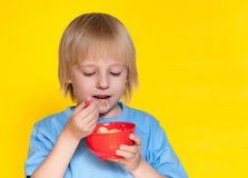 Boy kid child eating corn flakes cereal. Blond boy kid child eating corn flakes cereal royalty free stock image