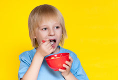 Boy kid child eating corn flakes cereal. Blond boy kid child eating corn flakes cereal royalty free stock photos