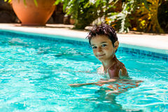 Boy kid child eight years old inside swimming pool portrait happy fun bright day Royalty Free Stock Photography