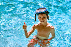 Boy kid child eight years old inside swimming pool portrait happy fun bright day diving goggles thumbs up Stock Photo