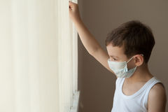 Boy kid epidemic flu medicine child  medical mask hospital. Kid standing at the window in the hospital  in medical mask Royalty Free Stock Photo