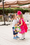 The boy kid gives flowers and kissing girl child on birthday. Stock Photo