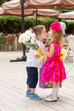 The boy kid gives flowers to girl child on birthday Royalty Free Stock Image