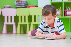 Boy kid lay down on floor and reading tale book in preschool li. Brary,Kindergarten school education concept stock photo