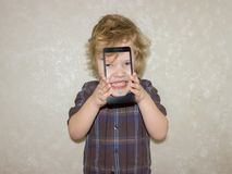 A boy kid looks into the camera of a smartphone, shows the screen with his digital photo. Toddler smiles at the camera and takes a selfie stock photography