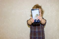 A boy kid looks into the camera of a smartphone, shows the screen with his digital photo. Toddler smiles at the camera and takes a selfie royalty free stock image