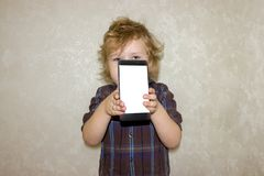 A boy kid looks into the camera of a smartphone, shows the screen with his digital photo. royalty free stock image