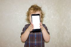 A boy kid looks into the camera of a smartphone, shows the screen with his digital photo. stock photography