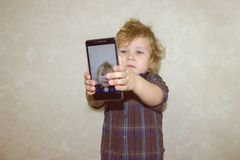 A boy kid looks into the camera of a smartphone, shows the screen with his digital photo. Toddler smiles at the camera and takes a selfie royalty free stock photo