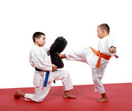 Boy in a kimono hits foot the kick simulator which in the hands of the other sportsman Stock Photo