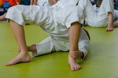 A boy in the kimono practicing karate on the floor royalty free stock photo