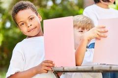 Boy in kindergarten tinkers with cardboard stock image