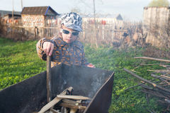 Boy kindle a fire in the grill Stock Photo