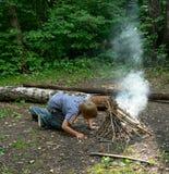 Boy Kindles Bonfire Royalty Free Stock Photos