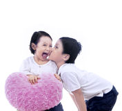 Boy kiss girl with heart pillow - isolated Stock Photo