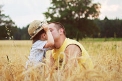 Boy kiss his father in the field Stock Photo