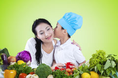Boy kiss his mother while preparing vegetables Royalty Free Stock Photo