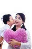 Boy kiss mother holding heart shape pillow on white. Background Stock Photography