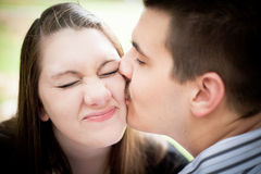 Boy Kisses Girl. A young men kissing a young women on the cheek while she makes a funny face Royalty Free Stock Photos