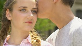 Boy kisses girl, concept of skincare in adolescence, no acne, self-confidence. Stock footage stock footage