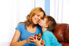 Boy kisses his mother in cheek when giving gift Royalty Free Stock Photo
