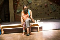 The boy kisses and hugs his mother. The climber rest after a workout. Training in the bouldering hall. The boy kisses and hugs his mother. A women trains with a royalty free stock image
